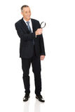 Businessman with a magnifying glass Royalty Free Stock Photos