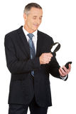 Businessman with magnifying glass and mobile phone Royalty Free Stock Photography