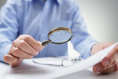Businessman with magnifying glass reading documents Royalty Free Stock Images