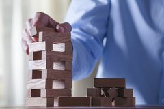 Businessman make a building with wood blocks Stock Photo