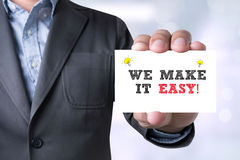 Businessman WE MAKE IT EASY!  message on the card shown Stock Images