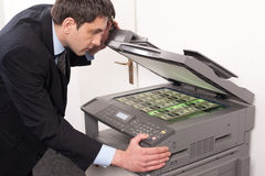 Businessman make false money on copy machine Royalty Free Stock Photos