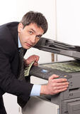 Businessman make false money on copy machine Royalty Free Stock Photo