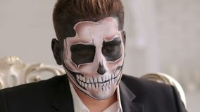 Businessman with make-up skeleton sitting in the old grey chair with closed eyes. Halloween or horror theme. Dead face make up portrait of young man in studio stock footage