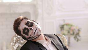 Man with make-up skeleton sitting in the chair and creepy looking at the camera. Businessman with make-up skeleton sitting in the old grey chair, and creepy stock footage