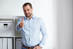 Businessman makes a gesture thumb. Young businessman makes a gesture thumb up in the office Stock Image