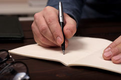 Businessman makes a note at notebook Royalty Free Stock Images