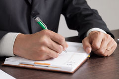 Businessman makes notes to his diary Stock Photo