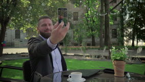 Businessman makes selfie during coffe break. Outdoor. Steadicam shot. He is young and has beard. He is dressed on shirt and jacket. At backgroung there is stock video footage