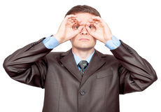 Businessman making binoculars with hands Royalty Free Stock Photos