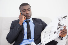 Businessman making a call while reading the paper on sofa Royalty Free Stock Photo