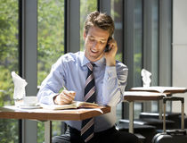 A businessman making a diary appointment whilst waiting to travel Stock Image