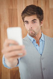 Businessman making face while taking selfie Stock Images