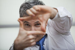 Man looking through finger frame. Man with blue tie looking through fingers that form a frame Stock Image