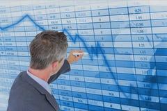 Businessman making graph on futuristic screen. Digital composite of Businessman making graph on futuristic screen Stock Photos