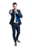 Businessman making keep a secret gesture standing on white backg Stock Image