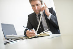 Businessman making a note in his diary Stock Images
