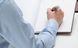 Businessman making notes in a datebook. Closeup shot Royalty Free Stock Photos