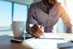 Businessman making notes at his desk. Business investor writing in notepad with a coffee cup on the desk. Closeup of a businessman& x27;s hand holding pen and Royalty Free Stock Photography