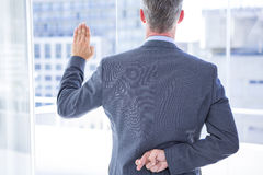 Businessman making a oath while crossing fingers Royalty Free Stock Images