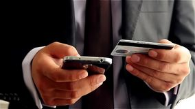 Businessman making online payment with credit card and smartphone