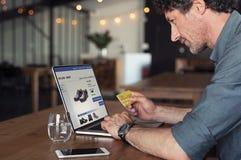 Businessman making online payment. Senior businessman using debit card to make online transaction using laptop. Mature business man doing shopping online banking stock image