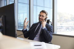 Businessman Making Phone Call Sitting At Desk In Office Royalty Free Stock Image