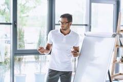 Businessman making presentation at white board in office. Concentrated businessman making presentation at white board in office Stock Photos