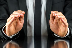 Businessman making a protective gesture. Businessman in a suit sitting at a desk making a protective gesture with his cupped hands reflected in the shiny surface royalty free stock photography