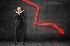 Businessman making rejection gesture with red arrow going down on black background. Risk management. Business solutions. Success and strategy concept stock photography