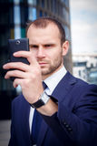 Businessman making selfie photo on smartphone. Very serious businessman making selfie photo on smartphone outside the office building Royalty Free Stock Image