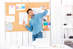 Businessman making selfie while standing in front of task board Royalty Free Stock Images