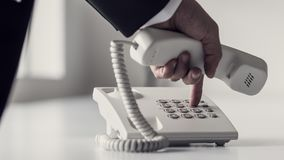 Dialing a phone number on a classical white landline device royalty free stock photos