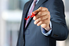 Businessman  making vote  by  a red  pen Royalty Free Stock Image