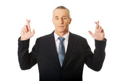 Businessman making a wish with fingers crossed Royalty Free Stock Photo