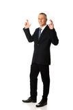 Businessman making a wish with fingers crossed Stock Image