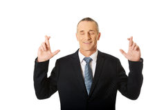 Businessman making a wish with fingers crossed Royalty Free Stock Images