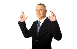 Businessman making a wish with fingers crossed Royalty Free Stock Image