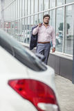 Businessman man goes to the car in the urban district Stock Photography