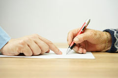 Businessman man is pointing senior where to sign contract.  Stock Images