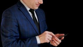 Businessman man in suit works on his smartphone, showing smile. Fingers touch the touch screen for typing. Management