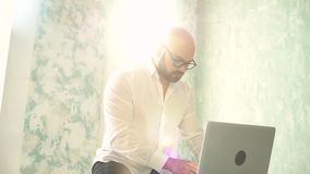 The bearded man with glasses in white using laptop indoors. Businessman working on laptop computer. Businessman or manager working on laptop computer. the stock video footage