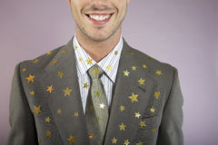 Businessman With Many Gold Stars On Suit. Closeup of a smiling young businessman with many gold stars on suit Stock Photography