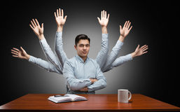 Businessman with many hands behind. Businessman with many hands at the table Royalty Free Stock Image