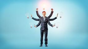 A businessman with many hands surrounded by light bulbs with one of them lighted up. Business ideas. Startups. Business angel royalty free stock images
