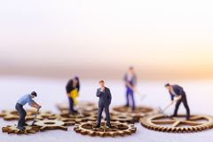 Businessman and many workers standing on wooden gear. Miniature businessman and many workers standing on wooden gear. Income and economic inequality concept royalty free stock photography