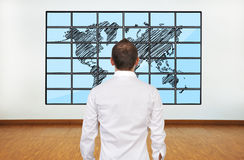 Businessman and map. Businessman looking at map of world on flat panels royalty free stock photography