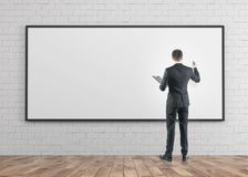 Businessman with a marker, whiteboard. Rear view of a businessman with a marker holding a clipboard. Concept of planning and education. A whiteboard background Stock Photo