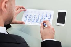 Businessman marking his dairy schedule checking for appointments Royalty Free Stock Photography