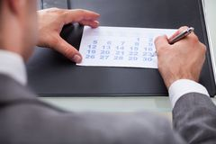 Businessman marking with pen and looking at date on calendar Royalty Free Stock Photo